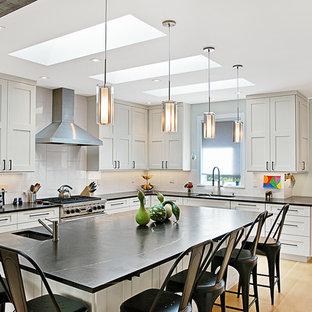 Diseño de cocina en L, tradicional renovada, con fregadero bajoencimera, armarios estilo shaker, puertas de armario grises, salpicadero blanco, electrodomésticos con paneles, suelo de madera clara, una isla, suelo beige y encimeras azules