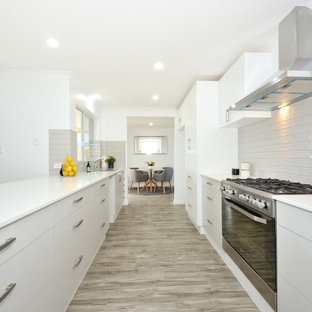Design ideas for a large contemporary galley eat-in kitchen in Perth with white cabinets, granite benchtops, grey splashback, stainless steel appliances, vinyl floors, grey floor, white benchtop, flat-panel cabinets and a peninsula.