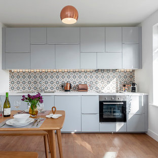 Small contemporary single-wall kitchen/diner in Wiltshire with flat-panel cabinets, blue cabinets, stainless steel appliances, light hardwood flooring, brown floors, a built-in sink and multi-coloured splashback.