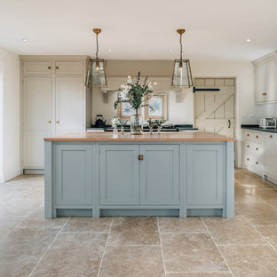Photo of a medium sized traditional l-shaped kitchen/diner in Cambridgeshire with a belfast sink, shaker cabinets, black appliances, an island, brown floors and beige cabinets.