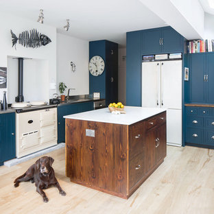 Design ideas for a traditional kitchen in London with an integrated sink, blue cabinets, stainless steel benchtops, white appliances, light hardwood floors, with island and beige floor.