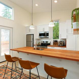 Idéer för att renovera ett litet skandinaviskt kök, med en undermonterad diskho, skåp i shakerstil, vita skåp, träbänkskiva, vitt stänkskydd, stänkskydd i tunnelbanekakel, rostfria vitvaror, korkgolv och en halv köksö