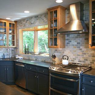ミルウォーキーの中サイズのインダストリアルスタイルのおしゃれなキッチン (アンダーカウンターシンク、シェーカースタイル扉のキャビネット、グレーのキャビネット、ソープストーンカウンター、ベージュキッチンパネル、石タイルのキッチンパネル、シルバーの調理設備の、淡色無垢フローリング) の写真