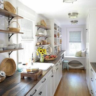 Ejemplo de cocina en U, marinera, sin isla, con despensa, fregadero encastrado, armarios con paneles empotrados, puertas de armario blancas, encimera de madera, suelo de madera oscura y suelo marrón