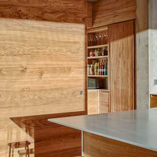 Inspiration for a large industrial single-wall open plan kitchen in Other with a built-in sink, flat-panel cabinets, medium wood cabinets, white splashback, black appliances, concrete flooring, an island and white worktops.