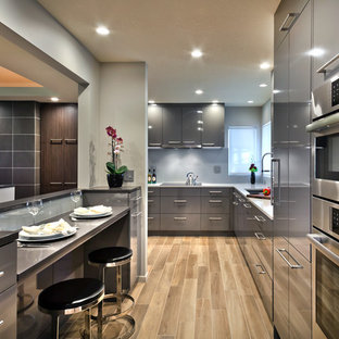 Mid-sized contemporary kitchen photos - Example of a mid-sized trendy kitchen design in Minneapolis with an undermount sink, flat-panel cabinets, gray cabinets, quartz countertops, gray backsplash, glass sheet backsplash and stainless steel appliances