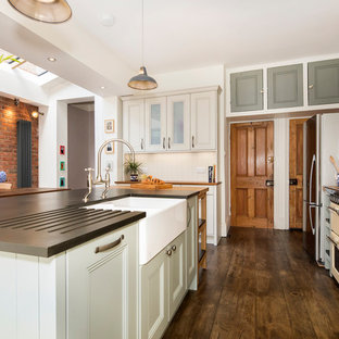 Design ideas for a large contemporary l-shaped kitchen/diner in Other with a belfast sink, shaker cabinets, grey cabinets, white splashback, ceramic splashback, integrated appliances, medium hardwood flooring, an island and brown floors.