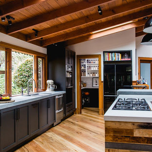 Inspiration for a large country galley kitchen in Melbourne with an undermount sink, shaker cabinets, black cabinets, quartz benchtops, white splashback, terra-cotta splashback, black appliances, medium hardwood floors, with island, brown floor and grey benchtop.