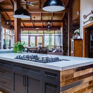 メルボルンの大きいラスティックスタイルのおしゃれなキッチン (アンダーカウンターシンク、シェーカースタイル扉のキャビネット、黒いキャビネット、クオーツストーンカウンター、白いキッチンパネル、テラコッタタイルのキッチンパネル、黒い調理設備、無垢フローリング、茶色い床、グレーのキッチンカウンター) の写真