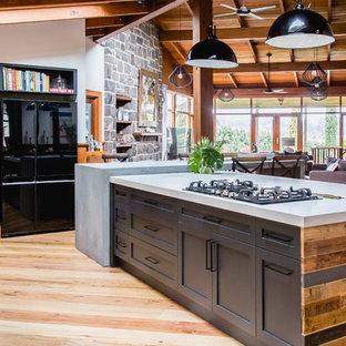 Idéer för ett stort rustikt grå kök, med en undermonterad diskho, skåp i shakerstil, svarta skåp, bänkskiva i kvarts, vitt stänkskydd, stänkskydd i terrakottakakel, svarta vitvaror, mellanmörkt trägolv, en köksö och brunt golv