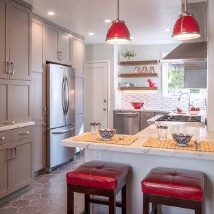 Foto på ett mellanstort vintage vit kök, med en undermonterad diskho, skåp i shakerstil, grå skåp, bänkskiva i kvarts, vitt stänkskydd, stänkskydd i porslinskakel, rostfria vitvaror, klinkergolv i porslin, en halv köksö och grått golv