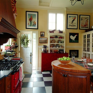 Mid-sized traditional l-shaped eat-in kitchen in Boston with beaded inset cabinets, coloured appliances, a farmhouse sink, medium wood cabinets, granite benchtops, brown splashback, ceramic splashback, ceramic floors, with island and multi-coloured floor.