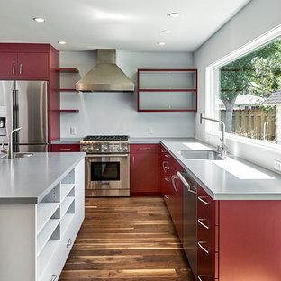 Mittelgroße, Offene Moderne Küche in L-Form mit Unterbauwaschbecken, flächenbündigen Schrankfronten, roten Schränken, Mineralwerkstoff-Arbeitsplatte, Küchengeräten aus Edelstahl, braunem Holzboden, Kücheninsel, braunem Boden, Küchenrückwand in Grau und grauer Arbeitsplatte in San Francisco