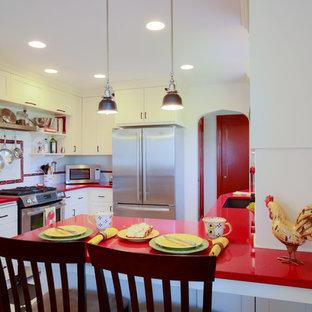 ポートランドの小さいエクレクティックスタイルのおしゃれなキッチン (アンダーカウンターシンク、白いキッチンパネル、サブウェイタイルのキッチンパネル、シルバーの調理設備の、白いキャビネット、シェーカースタイル扉のキャビネット、人工大理石カウンター、黒い床、赤いキッチンカウンター、クッションフロア) の写真