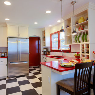 Bild på ett litet eklektiskt röd rött kök, med en undermonterad diskho, vitt stänkskydd, stänkskydd i tunnelbanekakel, rostfria vitvaror, skåp i shakerstil, vita skåp, bänkskiva i koppar, en halv köksö, svart golv och vinylgolv