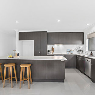 Inspiration for a beach style l-shaped kitchen in Other with a drop-in sink, flat-panel cabinets, grey cabinets, white splashback, stainless steel appliances, with island, grey floor and white benchtop.