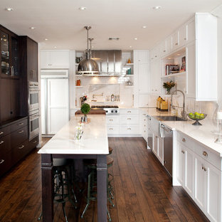 Large traditional enclosed kitchen remodeling - Enclosed kitchen - large traditional u-shaped dark wood floor and brown floor enclosed kitchen idea in Las Vegas with a farmhouse sink, shaker cabinets, white cabinets, white backsplash, stainless steel appliances, an island and marble countertops