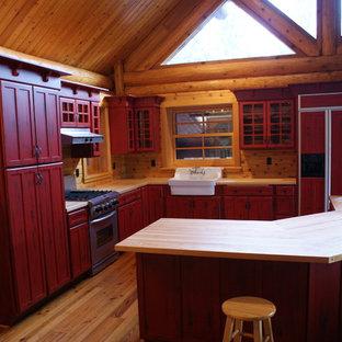 他の地域の広いラスティックスタイルのおしゃれなキッチン (落し込みパネル扉のキャビネット、赤いキャビネット、エプロンフロントシンク、木材カウンター、茶色いキッチンパネル、木材のキッチンパネル、パネルと同色の調理設備、無垢フローリング、茶色い床) の写真