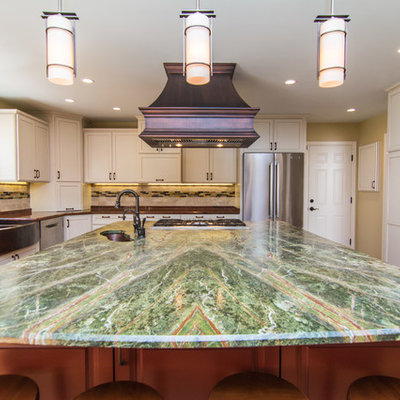 Example of a large eclectic medium tone wood floor eat-in kitchen design in DC Metro with a farmhouse sink, flat-panel cabinets, white cabinets, granite countertops, beige backsplash, stone tile backsplash, stainless steel appliances and an island