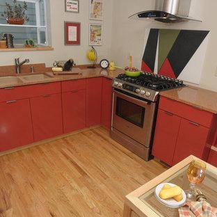 デンバーの中くらいのモダンスタイルのおしゃれなキッチン (アンダーカウンターシンク、フラットパネル扉のキャビネット、オレンジのキャビネット、御影石カウンター、オレンジのキッチンパネル、石スラブのキッチンパネル、シルバーの調理設備、淡色無垢フローリング) の写真
