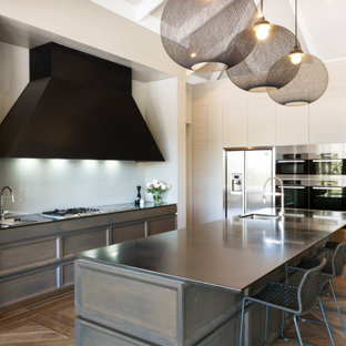 Design ideas for a large contemporary l-shaped kitchen in Melbourne with recessed-panel cabinets, quartz benchtops, white splashback, glass sheet splashback, stainless steel appliances, medium hardwood floors, with island, brown floor, vaulted, an undermount sink and dark wood cabinets.