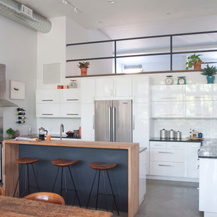 Contemporary eat-in kitchen inspiration - Trendy u-shaped eat-in kitchen photo in New York with flat-panel cabinets, white cabinets, white backsplash, subway tile backsplash, stainless steel appliances and an island