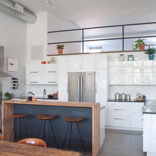 Свежая идея для дизайна: п-образная кухня в современном стиле с обеденным столом, плоскими фасадами, белыми фасадами, белым фартуком, фартуком из плитки кабанчик, техникой из нержавеющей стали и островом - отличное фото интерьера