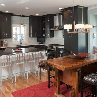 Mid-sized eclectic eat-in kitchen ideas - Mid-sized eclectic l-shaped medium tone wood floor and brown floor eat-in kitchen photo in Grand Rapids with an undermount sink, flat-panel cabinets, gray cabinets, quartz countertops, gray backsplash, marble backsplash, stainless steel appliances and an island