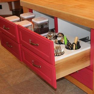 Пример оригинального дизайна: маленькая кухня в классическом стиле с обеденным столом, фасадами с утопленной филенкой, красными фасадами, деревянной столешницей, техникой из нержавеющей стали, полом из керамической плитки и островом