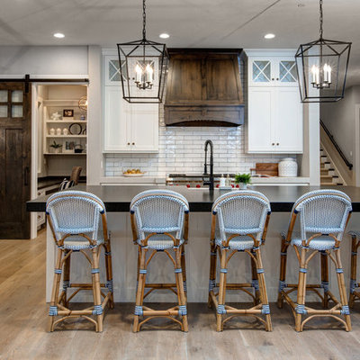 Large country single-wall medium tone wood floor open concept kitchen photo in Salt Lake City with a farmhouse sink, shaker cabinets, white cabinets, white backsplash, subway tile backsplash, stainless steel appliances, an island, soapstone countertops and black countertops