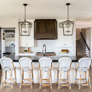 Inspiration for a large farmhouse single-wall medium tone wood floor open concept kitchen remodel in Salt Lake City with a farmhouse sink, white cabinets, white backsplash, subway tile backsplash, an island, shaker cabinets, soapstone countertops, stainless steel appliances and black countertops