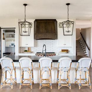 Inredning av ett lantligt stort svart linjärt svart kök med öppen planlösning, med en rustik diskho, vita skåp, vitt stänkskydd, stänkskydd i tunnelbanekakel, en köksö, skåp i shakerstil, bänkskiva i täljsten, rostfria vitvaror och mellanmörkt trägolv