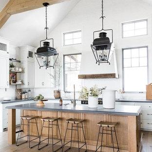 Idée de décoration pour une grande cuisine parallèle champêtre avec des portes de placard blanches, une crédence blanche, un électroménager noir, un sol en bois foncé, un îlot central, un plan de travail gris, un placard à porte shaker et un sol marron.