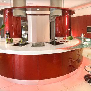 Ejemplo de cocina en U, moderna, grande, abierta, con fregadero integrado, armarios con paneles lisos, puertas de armario rojas, encimera de acrílico, salpicadero rojo, salpicadero de vidrio templado, electrodomésticos de acero inoxidable, suelo de baldosas de porcelana y península
