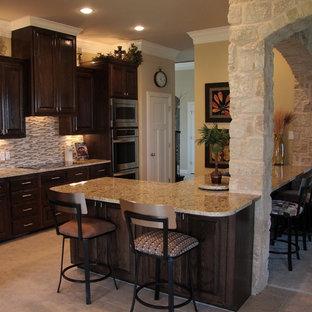 オースティンの地中海スタイルのおしゃれなキッチン (レイズドパネル扉のキャビネット、濃色木目調キャビネット、御影石カウンター、マルチカラーのキッチンパネル、ガラスタイルのキッチンパネル、シルバーの調理設備の、リノリウムの床) の写真