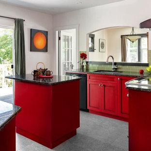 Klassische Küche mit Unterbauwaschbecken, Schrankfronten im Shaker-Stil, roten Schränken, Küchenrückwand in Grün, Rückwand aus Metrofliesen, schwarzen Elektrogeräten, Kücheninsel, grauem Boden und schwarzer Arbeitsplatte in Vancouver