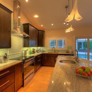 Exemple d'une cuisine bord de mer avec un évier encastré, des portes de placard en bois sombre, une crédence bleue, un électroménager en acier inoxydable, un sol en bois clair et un îlot central.