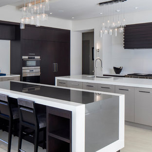 Design ideas for a large contemporary l-shaped kitchen in Orlando with flat-panel cabinets, quartz benchtops, white splashback, porcelain floors, multiple islands, an undermount sink, dark wood cabinets, stainless steel appliances and beige floor.
