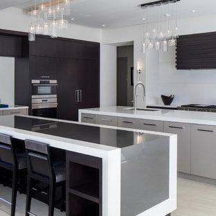 Inredning av ett modernt stort l-kök, med släta luckor, bänkskiva i kvarts, vitt stänkskydd, klinkergolv i porslin, flera köksöar, en undermonterad diskho, skåp i mörkt trä, rostfria vitvaror och beiget golv