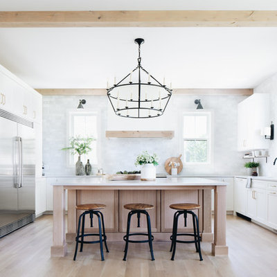 Farmhouse u-shaped light wood floor and beige floor eat-in kitchen photo in Chicago with an undermount sink, shaker cabinets, white cabinets, gray backsplash, stainless steel appliances, an island and white countertops