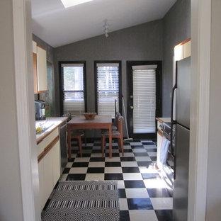 アトランタの小さいコンテンポラリースタイルのおしゃれなキッチン (フラットパネル扉のキャビネット、白いキャビネット、木材カウンター、シルバーの調理設備の、クッションフロア、アイランドなし、マルチカラーの床) の写真