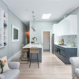 Mid-sized contemporary galley open plan kitchen in Sydney with an undermount sink, flat-panel cabinets, white cabinets, quartz benchtops, multi-coloured splashback, mosaic tile splashback, stainless steel appliances, light hardwood floors, a peninsula, brown floor and white benchtop.
