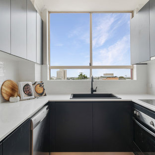 Inspiration for a contemporary u-shaped kitchen in Other with a drop-in sink, flat-panel cabinets, black cabinets, white splashback, stainless steel appliances and white benchtop.