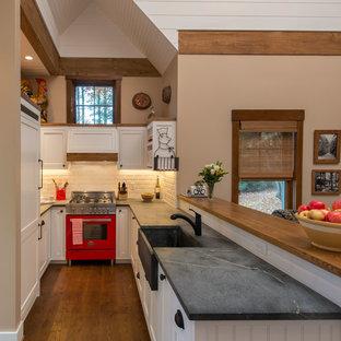 Inredning av ett lantligt litet kök, med en rustik diskho, skåp i shakerstil, vita skåp, bänkskiva i täljsten, vitt stänkskydd, stänkskydd i tunnelbanekakel, färgglada vitvaror, en halv köksö och mörkt trägolv