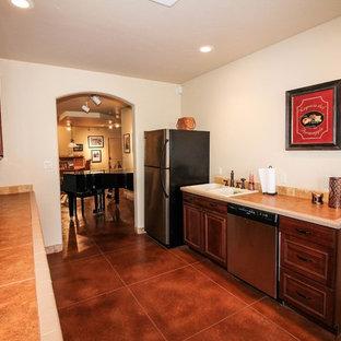 デンバーの地中海スタイルのおしゃれなII型キッチン (ドロップインシンク、レイズドパネル扉のキャビネット、濃色木目調キャビネット、タイルカウンター、ベージュキッチンパネル、トラバーチンの床、シルバーの調理設備の、コンクリートの床、茶色い床、ベージュのキッチンカウンター) の写真