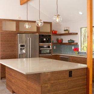 アルバカーキの大きいモダンスタイルのおしゃれなキッチン (アンダーカウンターシンク、フラットパネル扉のキャビネット、中間色木目調キャビネット、クオーツストーンカウンター、青いキッチンパネル、磁器タイルのキッチンパネル、シルバーの調理設備の、セラミックタイルの床、グレーの床) の写真