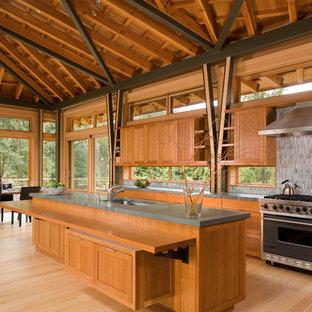 Inredning av ett modernt stort kök, med rostfria vitvaror, grått stänkskydd, en undermonterad diskho, skåp i mellenmörkt trä, bänkskiva i kalksten, ljust trägolv och en köksö