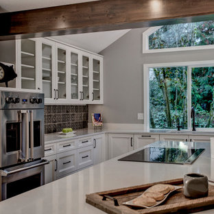 This is an example of a large transitional eat-in kitchen in Seattle with an undermount sink, recessed-panel cabinets, yellow cabinets, quartz benchtops, grey splashback, ceramic splashback, stainless steel appliances, medium hardwood floors, with island, brown floor and white benchtop.