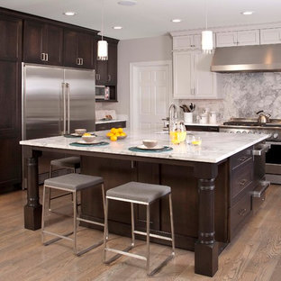 Inspiration for a mid-sized timeless u-shaped medium tone wood floor kitchen remodel in Seattle with an undermount sink, shaker cabinets, dark wood cabinets, marble countertops, white backsplash, stone slab backsplash, stainless steel appliances and an island