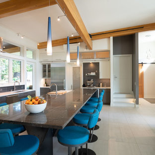 Photo of a contemporary l-shaped open plan kitchen in Seattle with a submerged sink, flat-panel cabinets, granite worktops, blue splashback, porcelain splashback, stainless steel appliances, porcelain flooring, an island, white floors and multicoloured worktops.